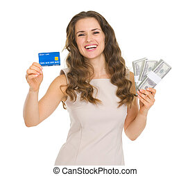 Happy young woman holding credit card and dollars packs