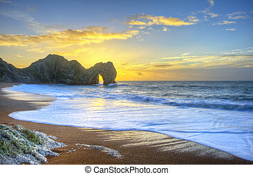 Vibrant sunrise over ocean with rock stack in foreground -...