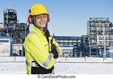 Industrial worker, posing in front of the main gate of a...