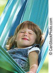 little girl on a hammock in nature