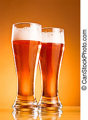 Two glass of beer over yellow background