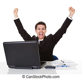 Businessman sitting at his desk rejoicing throwing his arms...