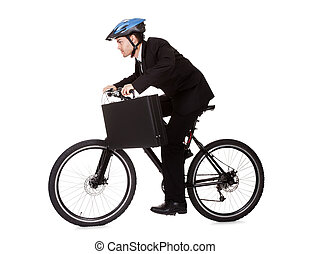 Businessman riding a bicycle to work in his suit exercising...