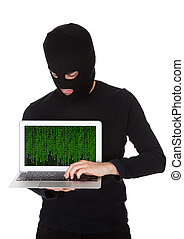 Hacker stealing data from a laptop - Hacker dressed in black...