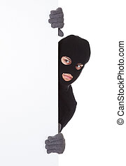 Thief looking around a blank sign - Thief in a balaclava and...
