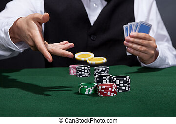 Poker player increasing his stakes throwing tokens onto the...