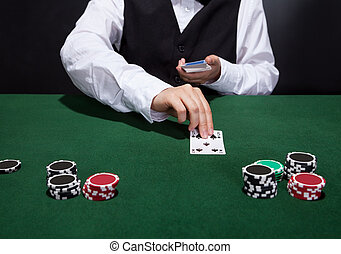 Croupier dealing cards in a poker game placing them face up...