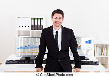 Confident smiling stock broker sitting on the edge of his...