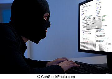 Hacker downloading information off a computer - Masked...