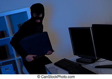 Thief steeling a computer - Man dressed in black and wearing...