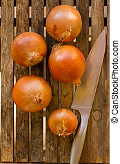 onion bulbs and knife on wooden board
