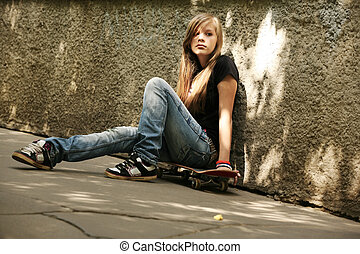 Skateboard - The girl with skateboard sitting against awall