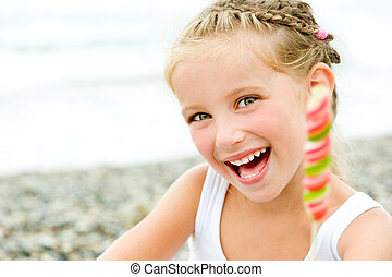 little girl on the beach - smily little girl with a candy on...
