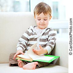 Little boy is reading book while sitting on couch, indoor...