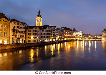 Illuminated Saint Peter Church and Houses along Limmat River...