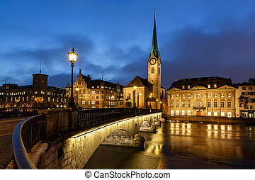 Illuminated Fraumunster Church and River Limmat in Zurich,...