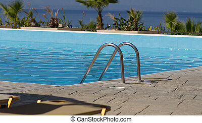 Bright blue swimming pool - Railing of the clean shiny...