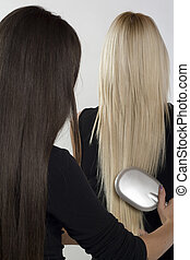 Combing through hair - Two women with perfect long brown and...
