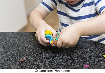 Toddler playing with multicoloured playdough