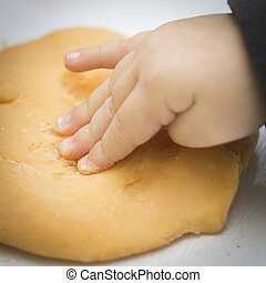 Childs hand presses playdough