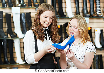 two woman choosing shoes in footwear store