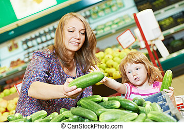 woman and little girl shopping fruits - woman and little...