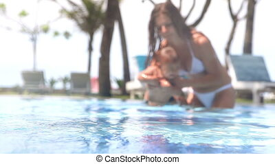 Under water - Beautiful happy mother teaching daughter to...