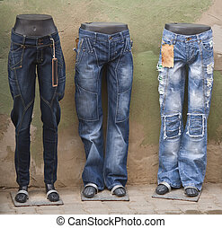 Blue jeans on manequins in an old town street.