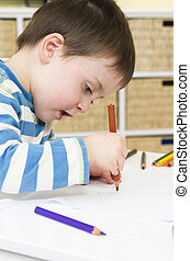 Toddler draws with a brown pencil