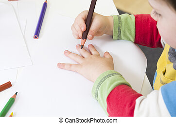 Toddler about to draw an outline of his hand