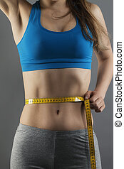 closeup of a woman measuring her waist on gray background