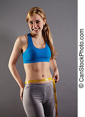 happy fitness woman measuring her waist on gray background