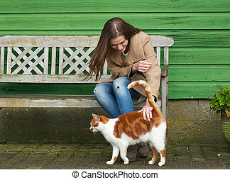 Girl's Bestfriend - Cute girl petting a furry cat outdoor....