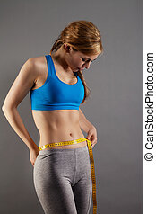 blonde fitness woman measuring her waist on gray background