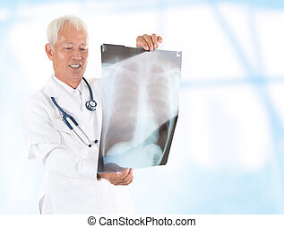 Asian senior doctor checking on x-ray image inside hospital...