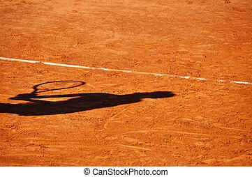 Tennis player shadow on a clay tennis court