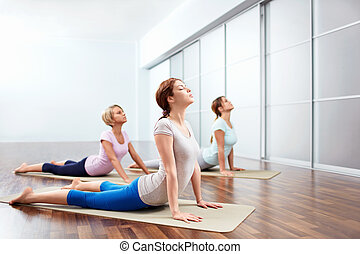 Exercise - Young girls do yoga indoors
