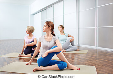 Group yoga sessions - Young attractive girls do yoga