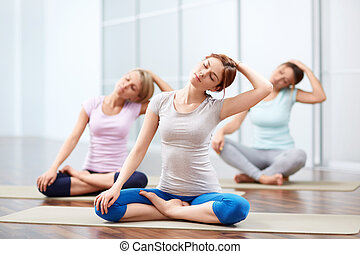 Group yoga sessions - Young girls do yoga indoors