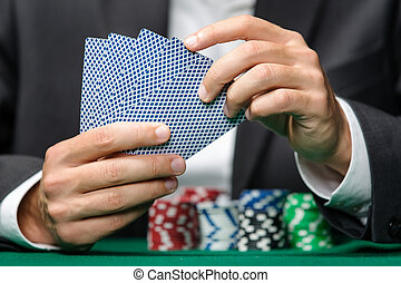 Gambler playing poker cards with poker chips on the table -...