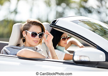 Close up view of girls in sunglasses in the automobile