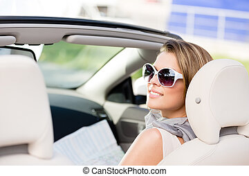 Girl with the road map in the car - Girl checks the way with...