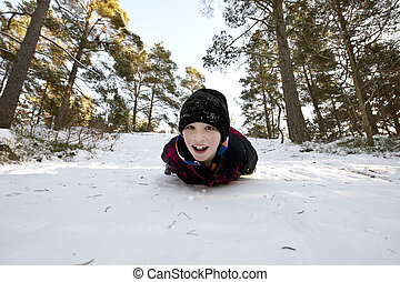 Gliding in the snow on belly - Young boy gliding on his...