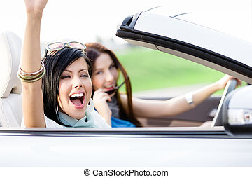 Two happy friends ride the cabriolet - Two happy friends in...