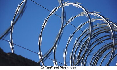 Razor Wire Against a Blue Sky - A dolly, close up shot of...