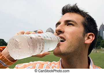 Man drinking Water - man drinking water in a city park