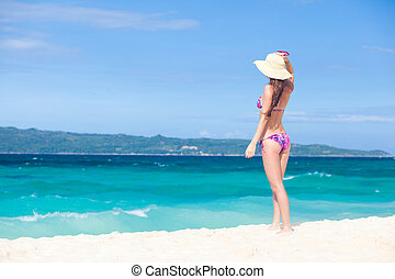 Beautiful young woman standing on the beach enjoying the sun