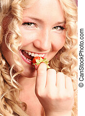 blonde curly girl biting strawberry