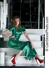 Young woman in long green dress sitting on stairs