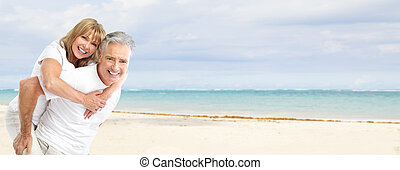 Happy senior couple on the beach. Exotic luxury resort.